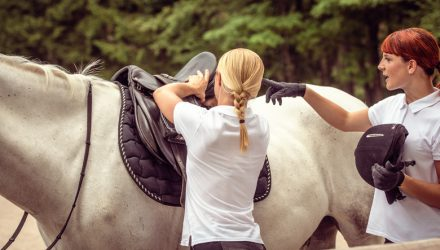 Mentor saddling a white horse for her student, who is pointing at the saddle and holding a helmet. Trees in the background.